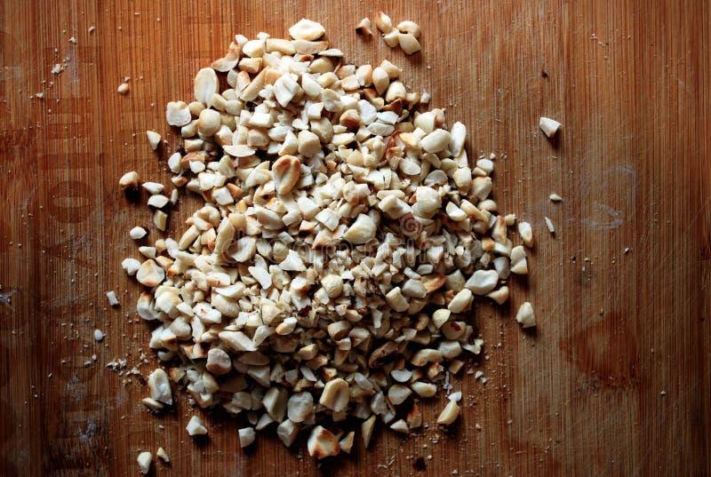 Krossade grillade jordnötter på ett bräde Stora och små stycken för att laga mat färgrika foods royaltyfri fotografi