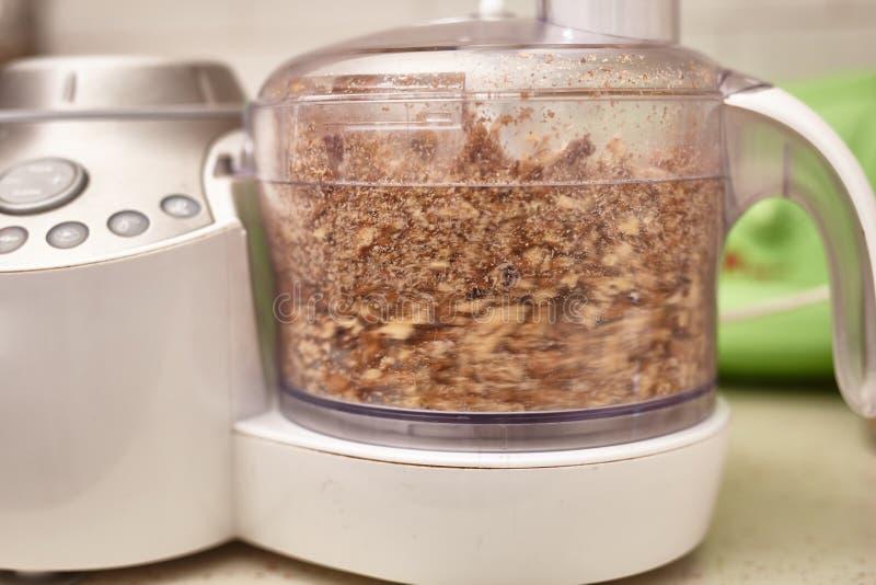 Krossade kärnavalnötter i matberedare royaltyfri foto