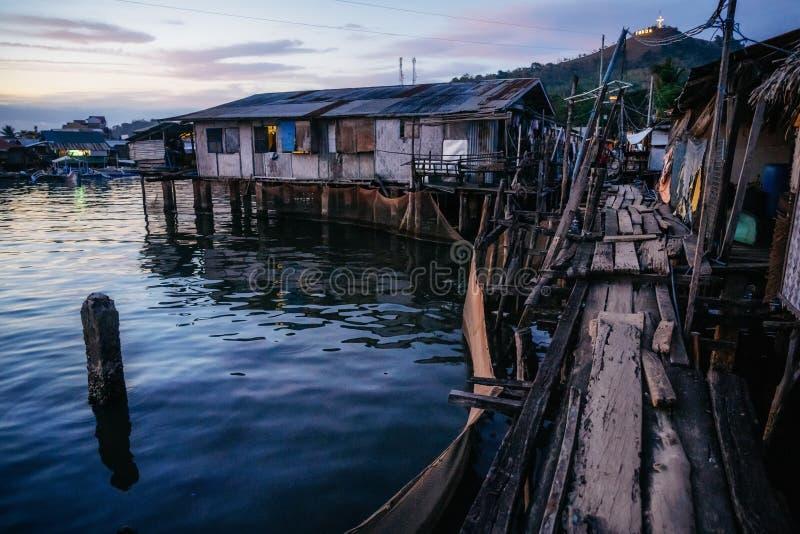 Krottenwijken met blokhuizen dichtbij water, Coron-stad, Palawan, Filippijnen stock fotografie