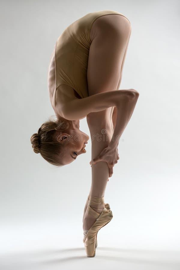 Krucha balerina bierze głębokiego skłon naprzód zdjęcia stock