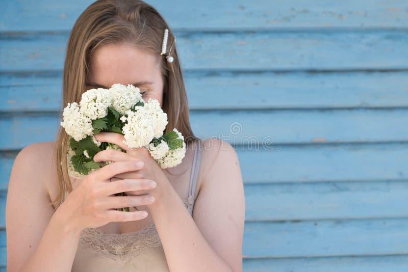 Krucha dziewczyna z blondynem zakrywa jej twarz z małym bukietem biali kwiaty, długie włosy dekorujący z hairpins z fotografia royalty free