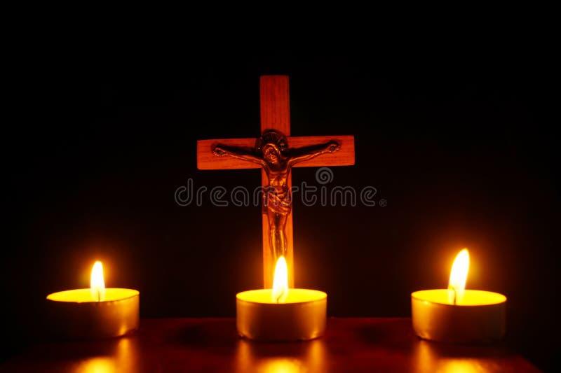 Krucyfiks i trzy płonącej świeczki w ciemności Ono modli się Jesu obraz stock