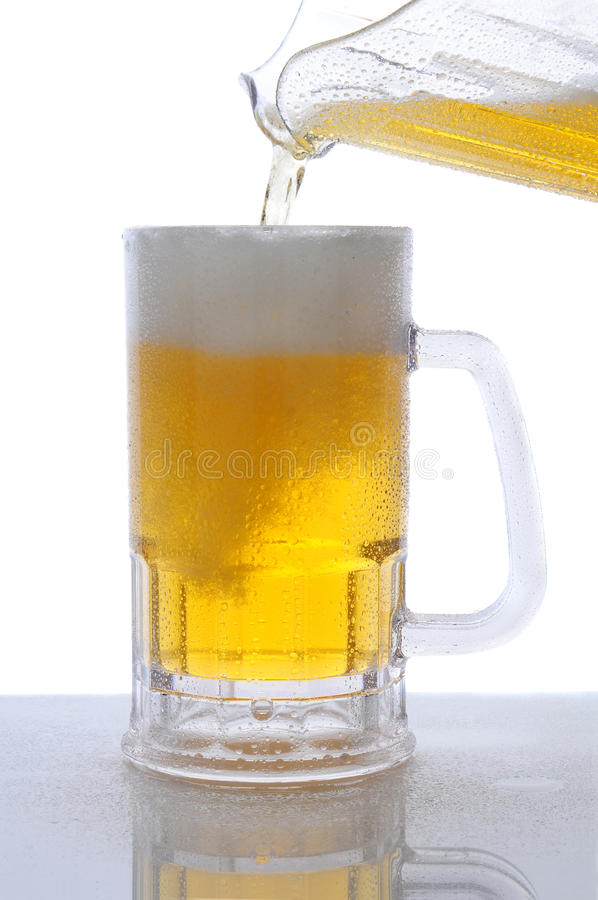 Krug Bier gießend in Becher stockfoto