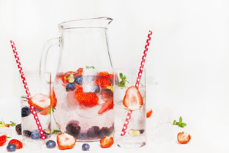 Krug mit Beerensommergetränk und zwei Gläser auf weißem hölzernem Hintergrund Detoxgetränk stockfotos