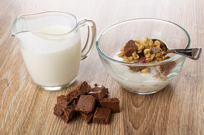 Krug mit Jogurt, Schüssel mit Granola, Jogurt, Schokolade, Stücke poröse Schokolade auf Tabelle stockbild