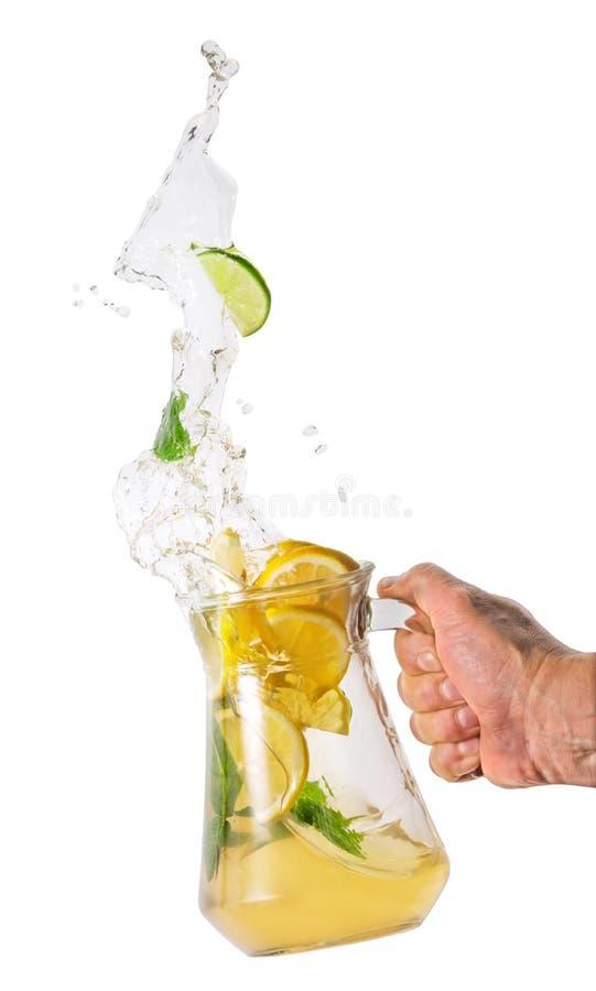 Krug mit Limonadenspritzen in der Hand lizenzfreies stockfoto