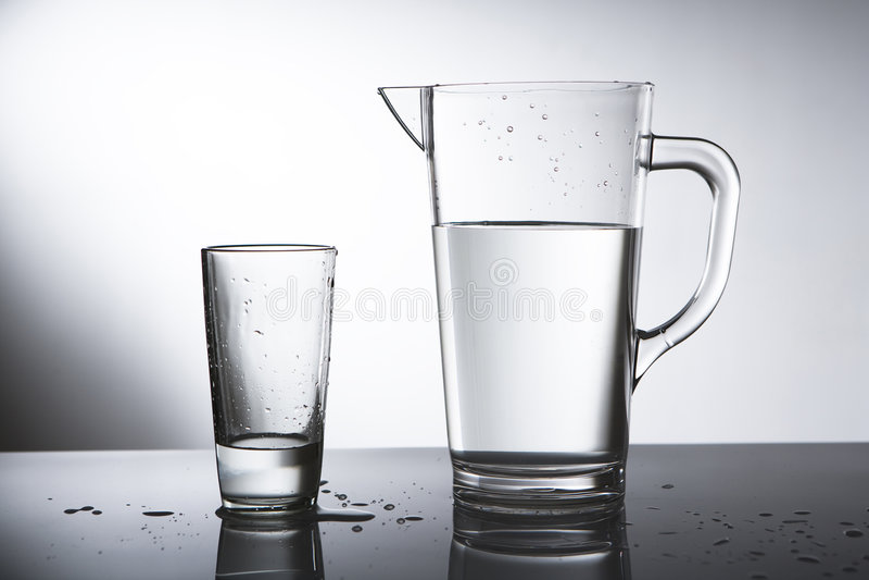 Krug Wasser mit Glas lizenzfreie stockbilder