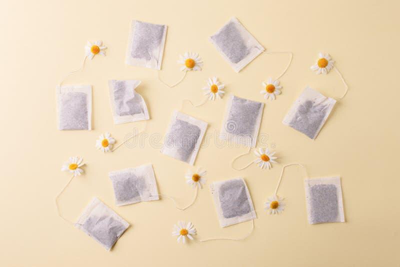 Kruiden alternatieve geneeskundereeks: Kamillebloemen en theezakjes op gele achtergrond Seizoengebonden anti-depressie, maag en stock foto