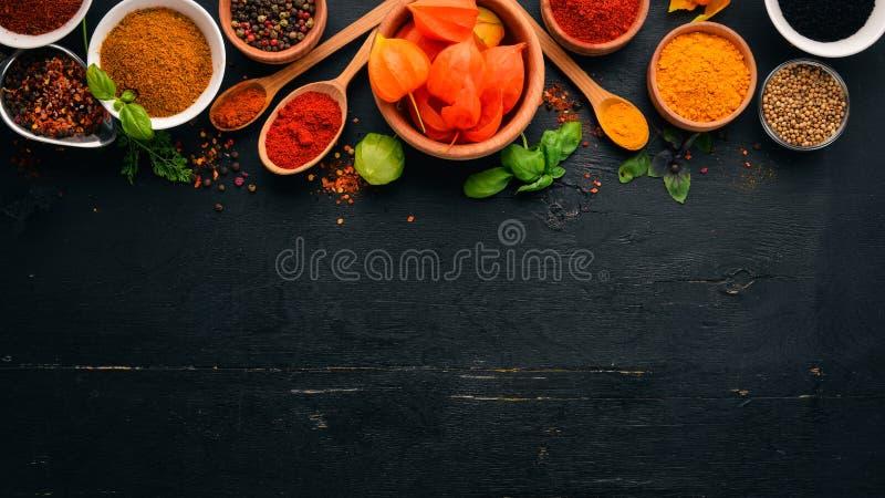 Kruiden en kruiden op een houten raad Peper, zout, paprika, basilicum, kurkuma Op een zwart houten bord stock afbeelding
