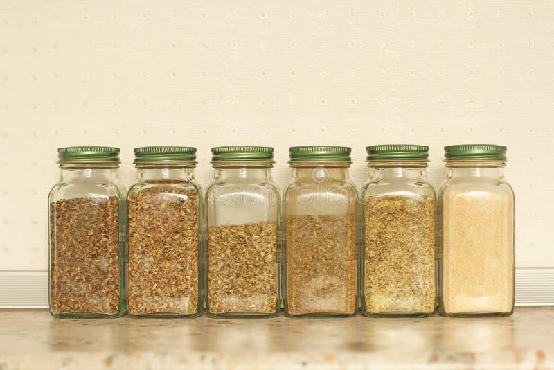 Kruiden in glaskruiken op een lichte achtergrond in de keuken Basilicum, orego, Italiaanse kruiden exemplaar ruimte voor uw tekst royalty-vrije stock afbeelding