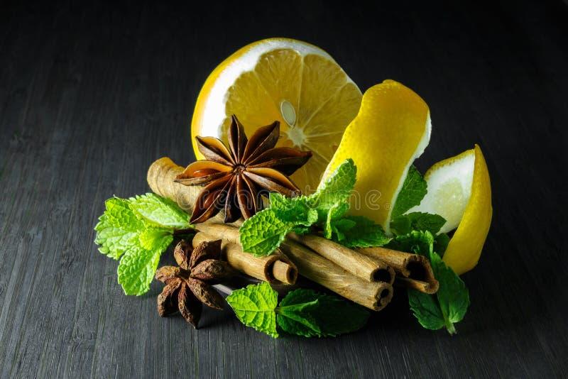 Kruiden; munt, steranijsplant, kaneel, citroen op een donkere boom stock fotografie