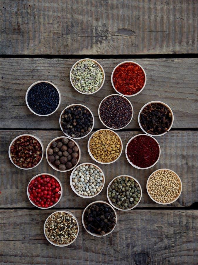 Kruiden op een houten achtergrond Koriander, zwarte peper, paprika, mosterd, kurkuma, komijn, sumac, fenegriek, kruidnagels, cube stock afbeelding