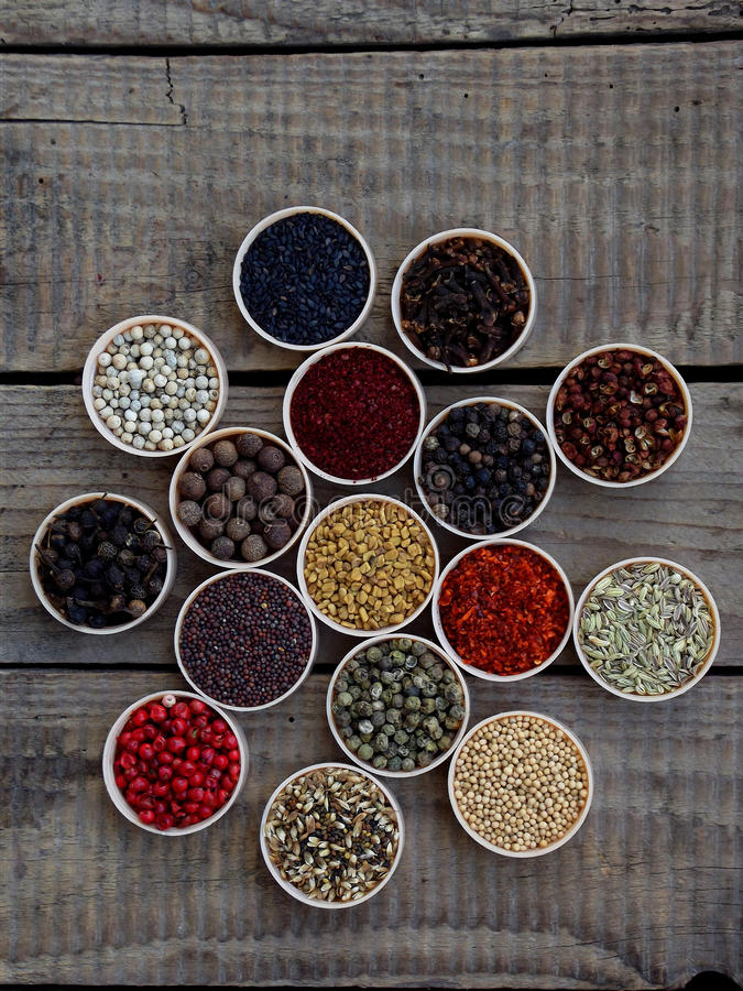 Kruiden op een houten achtergrond Koriander, zwarte peper, paprika, mosterd, kurkuma, komijn, sumac, fenegriek, kruidnagels, cube royalty-vrije stock afbeeldingen