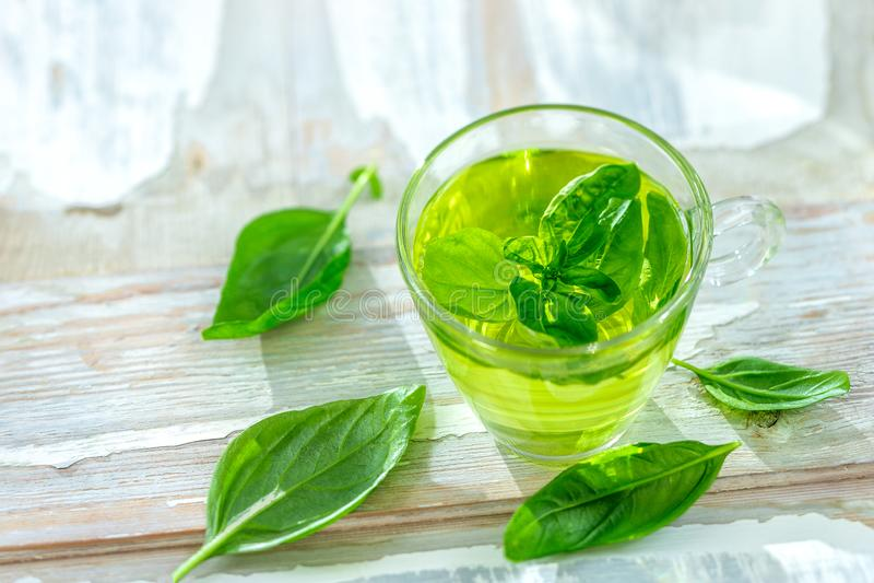 Kruidengeneesmiddelen : Calming tea in een theebeker met basilicumbladeren op een keukentafel royalty-vrije stock foto