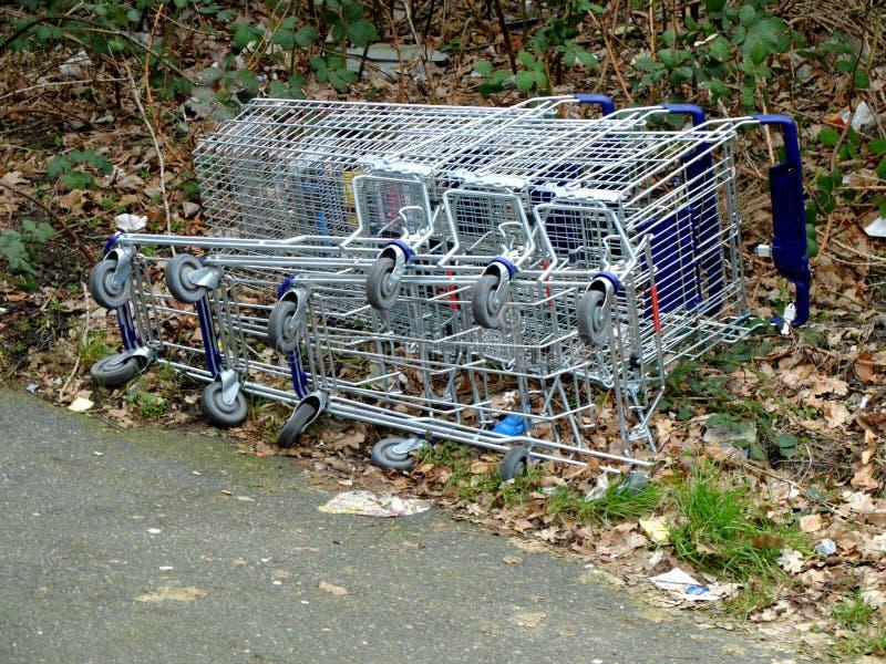 Kruidenierswinkelkarren gevallen en leggend op de grond Het concept lege supermarkten, daling in verkoop, sluit omhoog van superm stock foto's