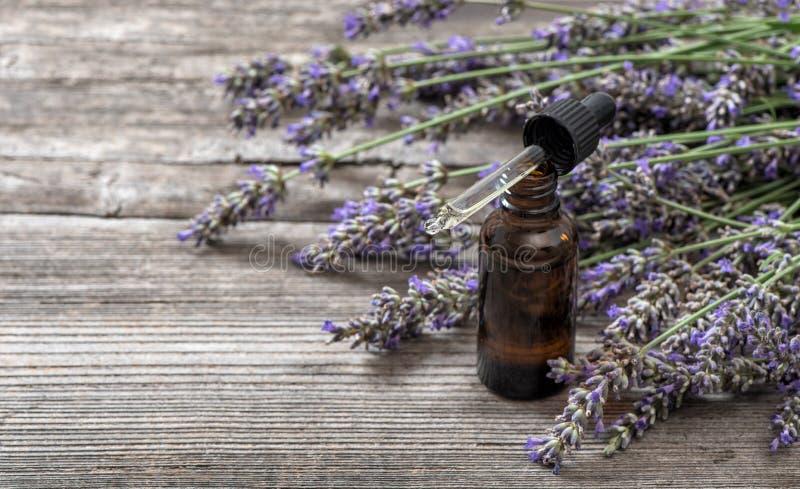Kruidenolie en lavendelbloemenboeket op houten achtergrond stock foto