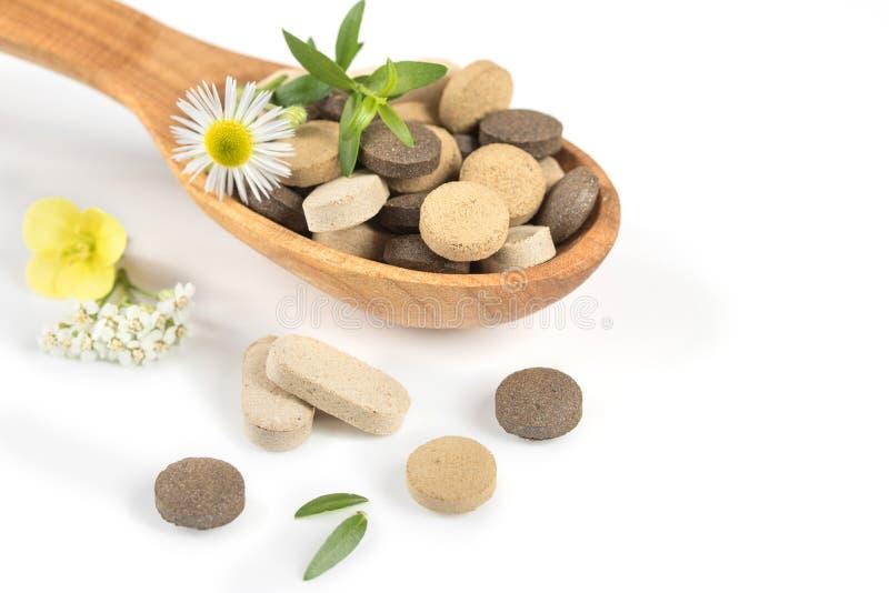 Kruidenpillen in een houten lepel met verse kruiden en bloemen voor alternatieve geneeskunde stock afbeelding