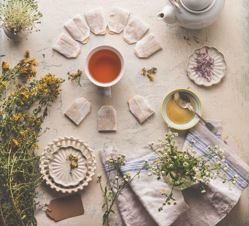 Kruidentheeconcept Gezonde warme drank Diverse verse medische kruiden met een bekertje kruidenthee, honing en theezakken op bijtt stock afbeeldingen
