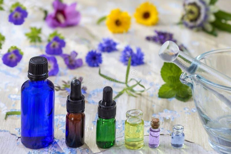 Kruidentherapie de etherische oliën en de medische bloemen en de kruiden op oude blauwe gebarsten houten achtergrond kopiëren rui stock foto's