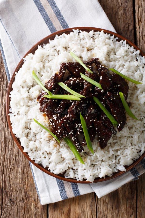 Kruidig Mongools rundvlees met rijstclose-up Verticale hoogste mening stock fotografie