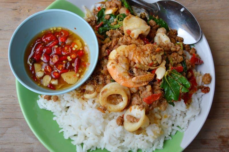 Kruidige be*wegen-gebraden gemengde zeevruchten en fijngehakt varkensvlees met basilicumblad op rijst stock foto