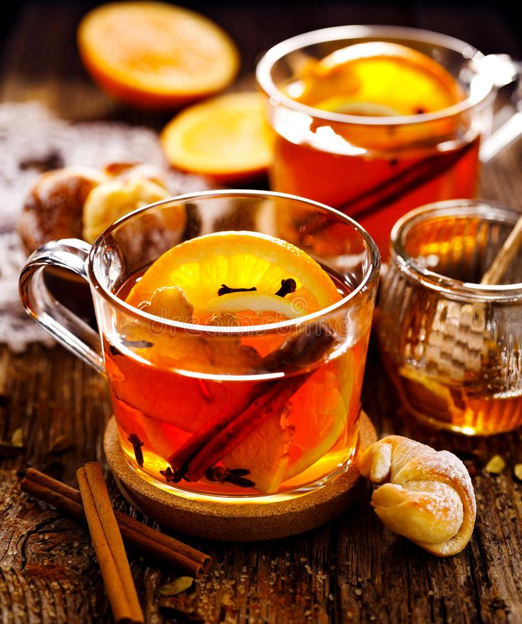 Kruidige citrusvruchten hete thee met gember, kruidnagels, kaneel en oranje plakken die, heerlijk, en gezond in glaskoppen verwar stock foto's