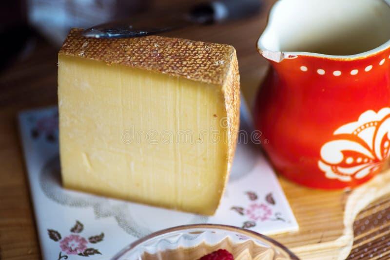 Kruidige harde kaas en rode oude waterkruik royalty-vrije stock fotografie