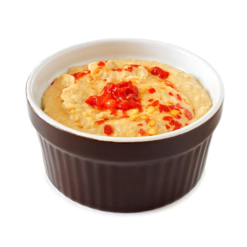 Kruidige hummus met hete peper in ramekinkom over wit royalty-vrije stock foto