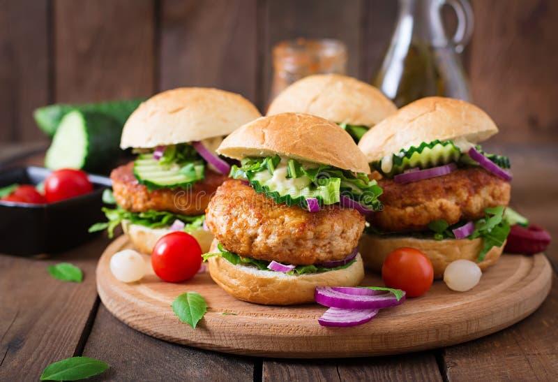 Kruidige kippenburgers met tomaat en aubergine - sandwich stock foto