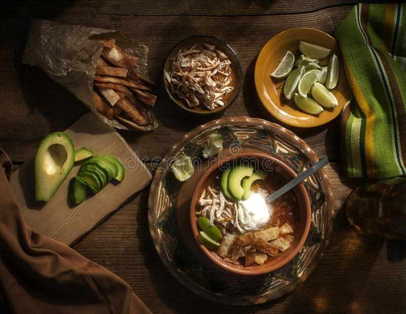 Kruidige Mexicaanse soep met room avocado, kalk, kippenborst en tortilla royalty-vrije stock fotografie