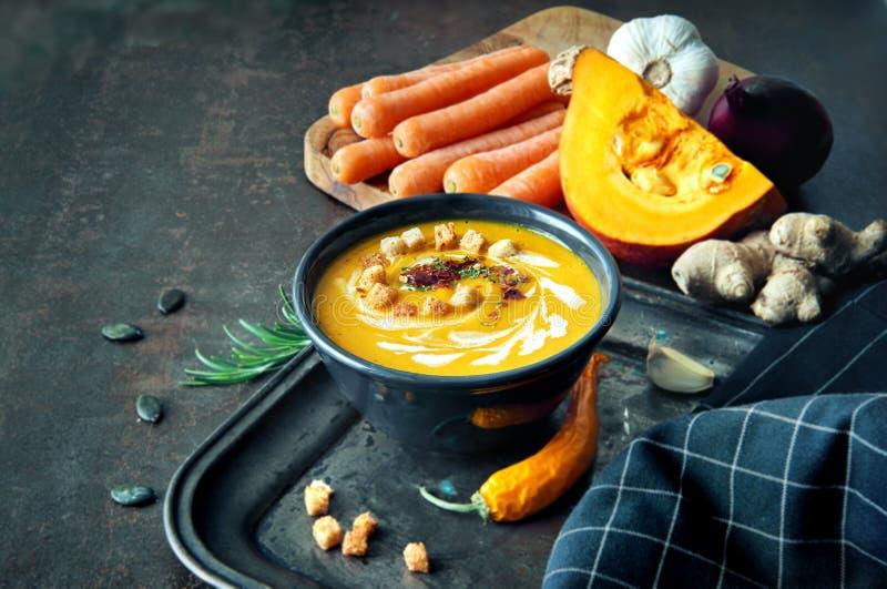 Kruidige pompoen en wortelsoep met gember, knoflook, rode ui en stock afbeelding