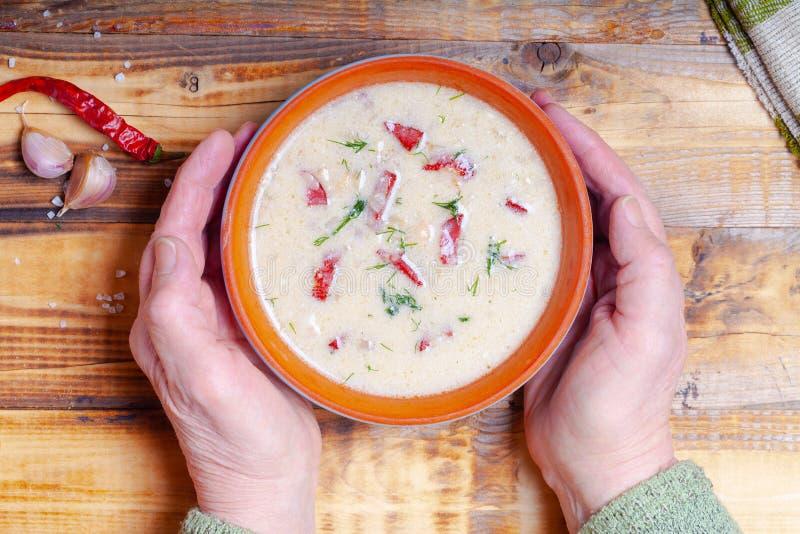 Kruidige soep met zure room, brood en kruiden op gebrande houten lijst Traditioneel landelijk diner De oude vrouwenhanden houdt k stock afbeeldingen