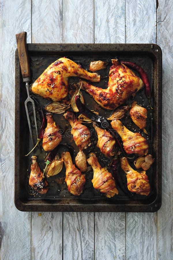 Kruidige verglaasde en bacon verpakte die kippenbenen met uien en Spaanse peper worden gebakken royalty-vrije stock foto's