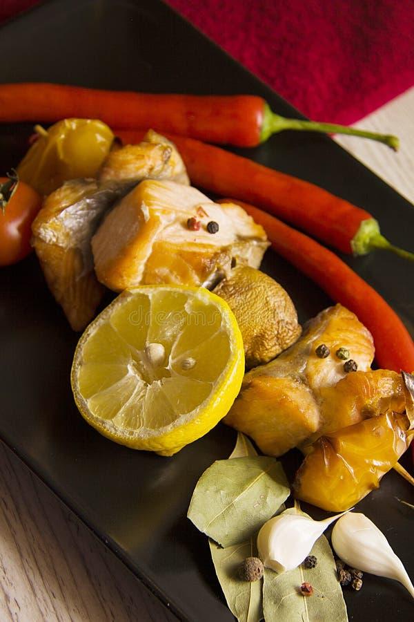 Kruidige vissen met tomaten stock afbeelding