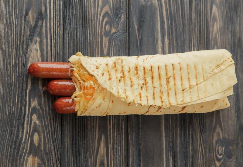 Kruidige worsten in pitabroodje op houten achtergrond Foto met exemplaarruimte stock afbeelding
