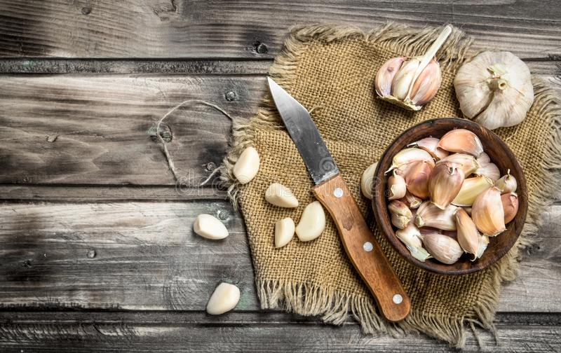 Kruidnagels van knoflook in een kom met een mes royalty-vrije stock afbeeldingen