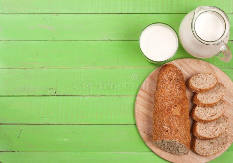 Kruik en glas melk met een brood van brood op een groene houten achtergrond met exemplaarruimte voor uw tekst Hoogste mening royalty-vrije stock afbeeldingen