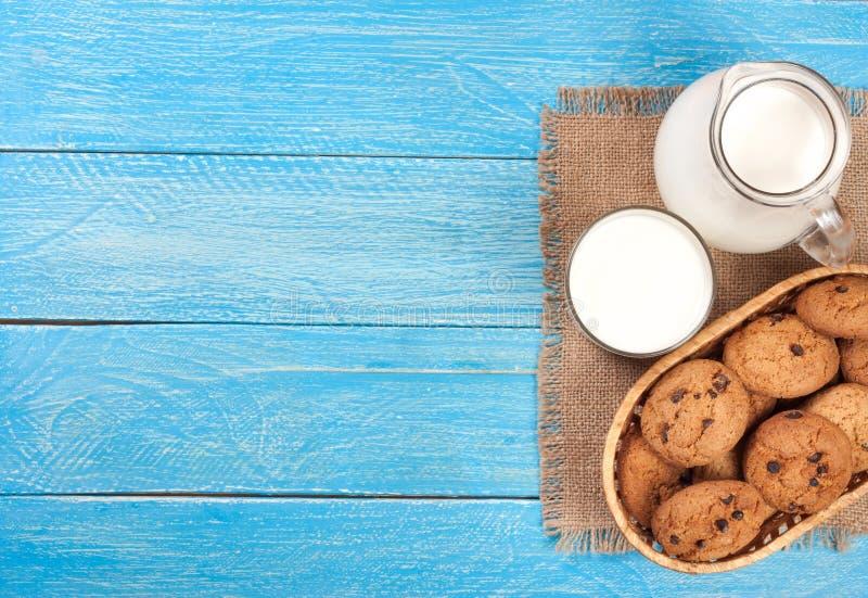 Kruik en glas melk met havermeelkoekjes op een blauwe houten achtergrond met exemplaarruimte voor uw tekst Hoogste mening stock fotografie
