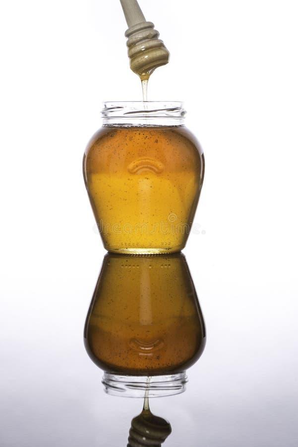 Kruik honing met dipper wordt weerspiegeld die royalty-vrije stock afbeeldingen