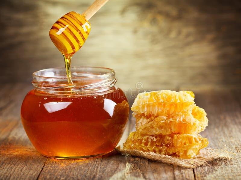 Kruik honing met honingraat stock foto's