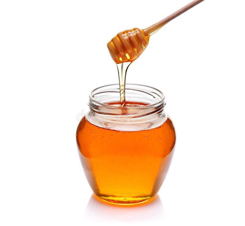 Kruik honing met houten drizzler stock foto's