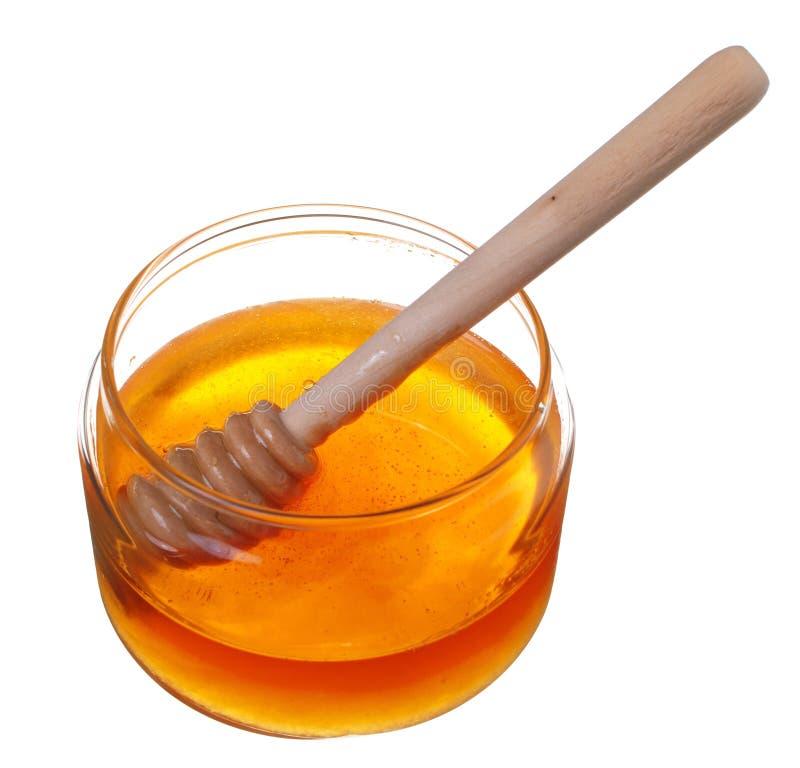 Kruik honing met houten drizzler die op witte achtergrond wordt geïsoleerd royalty-vrije stock afbeeldingen