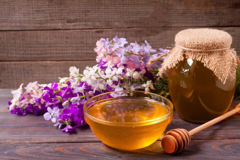 Kruik honing met wildflowers op een donkere houten achtergrond royalty-vrije stock afbeeldingen
