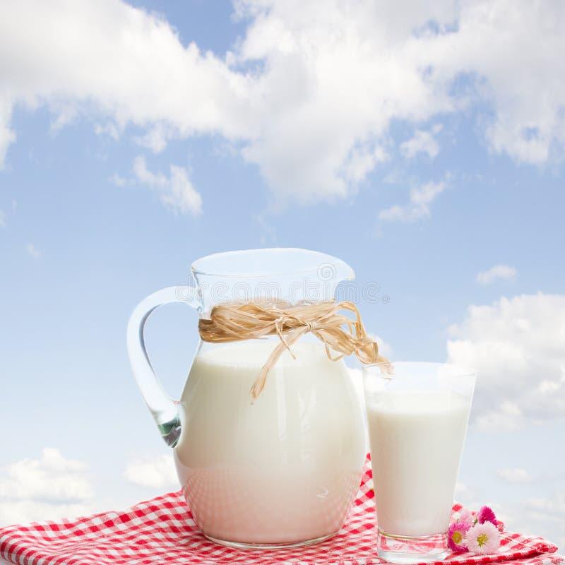 Kruik melk en glas openlucht royalty-vrije stock fotografie