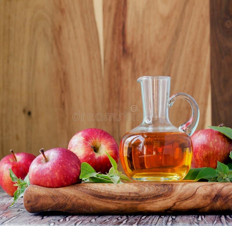 Kruik met de azijn van de appelcider en rijpe rode appelen op houten lijst, selectieve nadruk royalty-vrije stock fotografie