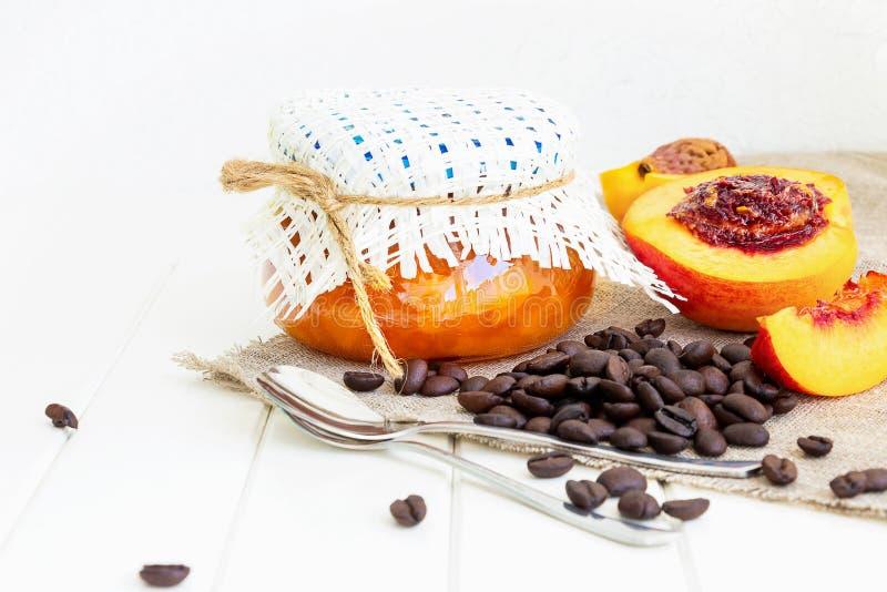 Kruik met perzik of nectarinejam Halve nectarinevruchten Koffiebonen op juteservet Witte Houten Achtergrond Selectieve nadruk C royalty-vrije stock foto