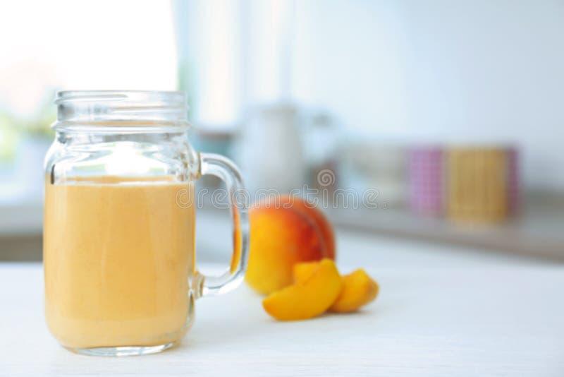 Kruik met smakelijke smoothie en perzik royalty-vrije stock afbeeldingen