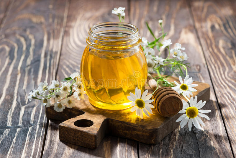 Kruik met verse bloemhoning op een donkere houten lijst stock foto