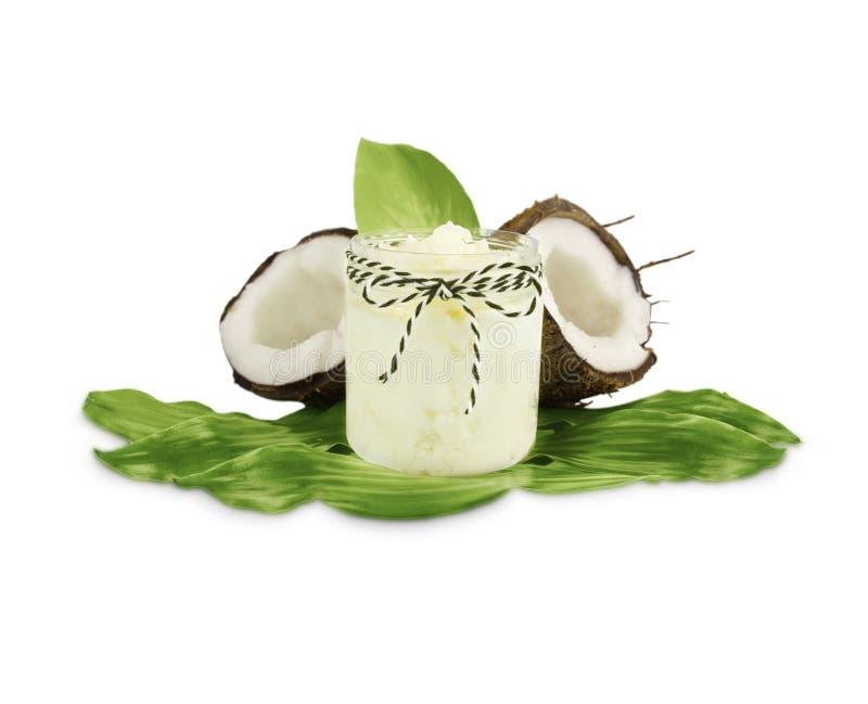 Kruik van kokosnotenolie en verse die kokosnoten op witte achtergrond wordt geïsoleerd stock foto