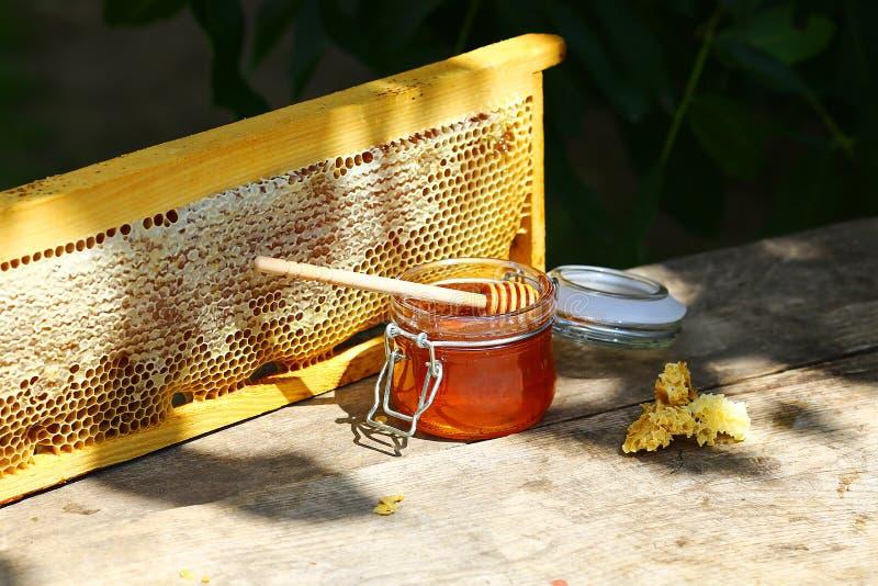 Kruik verse honing in een glaskruik op een oude lijst aangaande een bijenstal buiten kader met de structuurhoogtepunt van de bije stock afbeeldingen